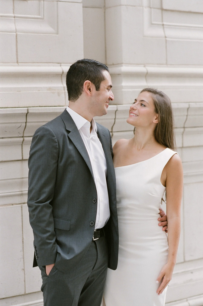 Bride and groom gaze at one another during their Chicago engagement session near the Wrigley Building