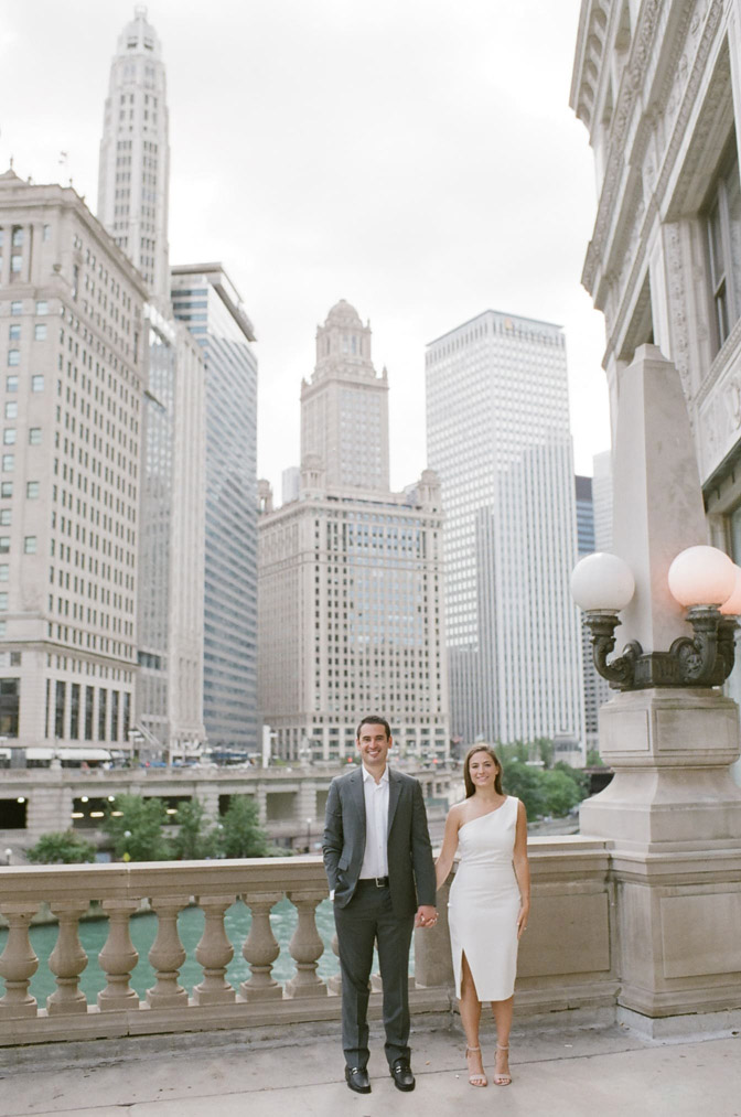 Couple holds hands during their engagement portraits along the Chicago Riverwalk