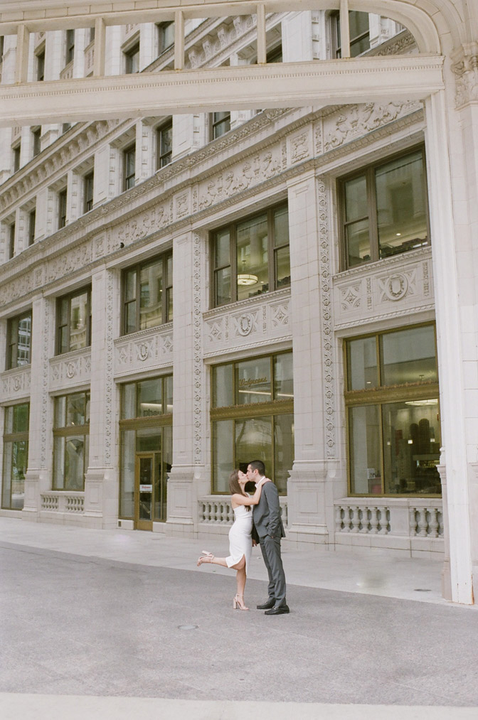 Bride and groom kiss during their Chicago engagement session near the Wrigley Building