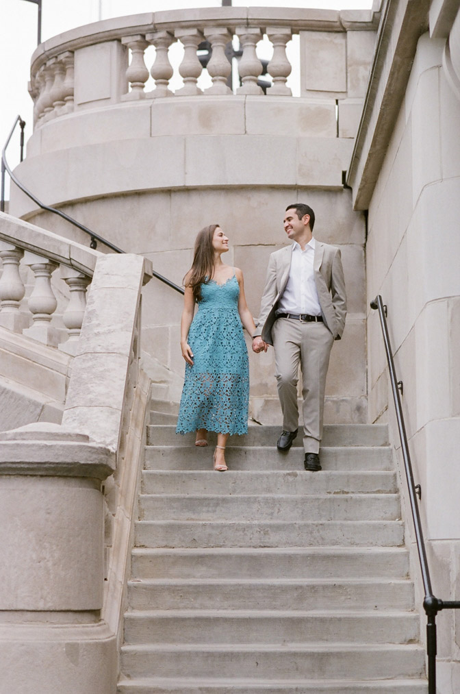 Couple holding hands while walking down stairs during their engagement portraits in Chicago