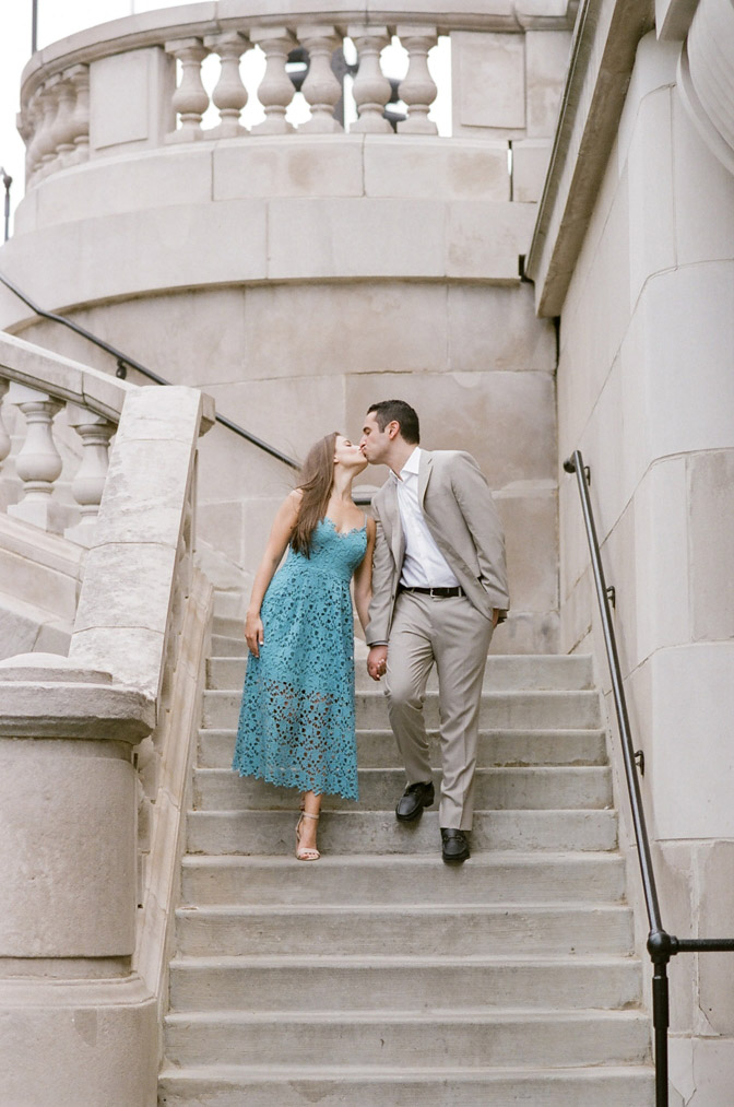 Couple holding hands and kissing during engagement portraits in Chicago