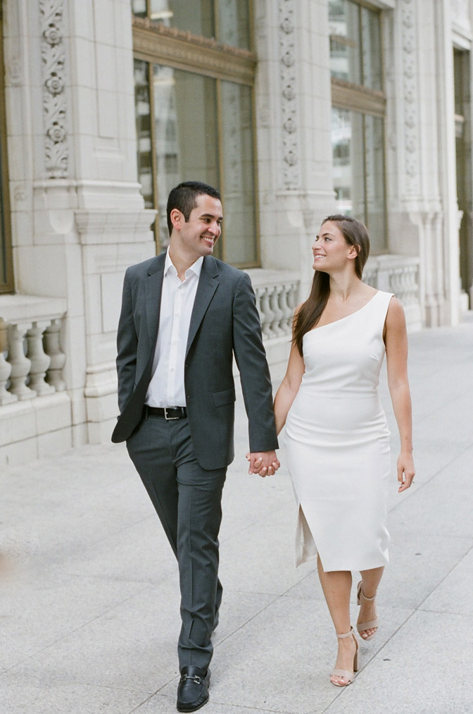 Bride and groom hold hands during their Chicago engagement session near the Wrigley Building