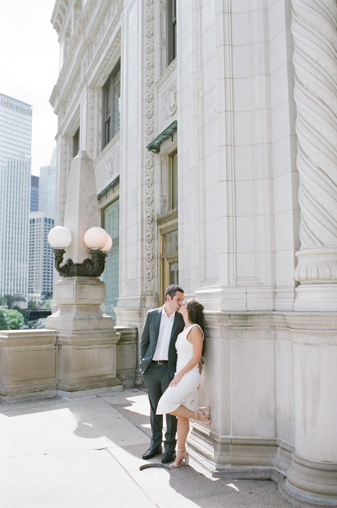 Bride and groom pose during their Chicago engagement session near the Wrigley Building