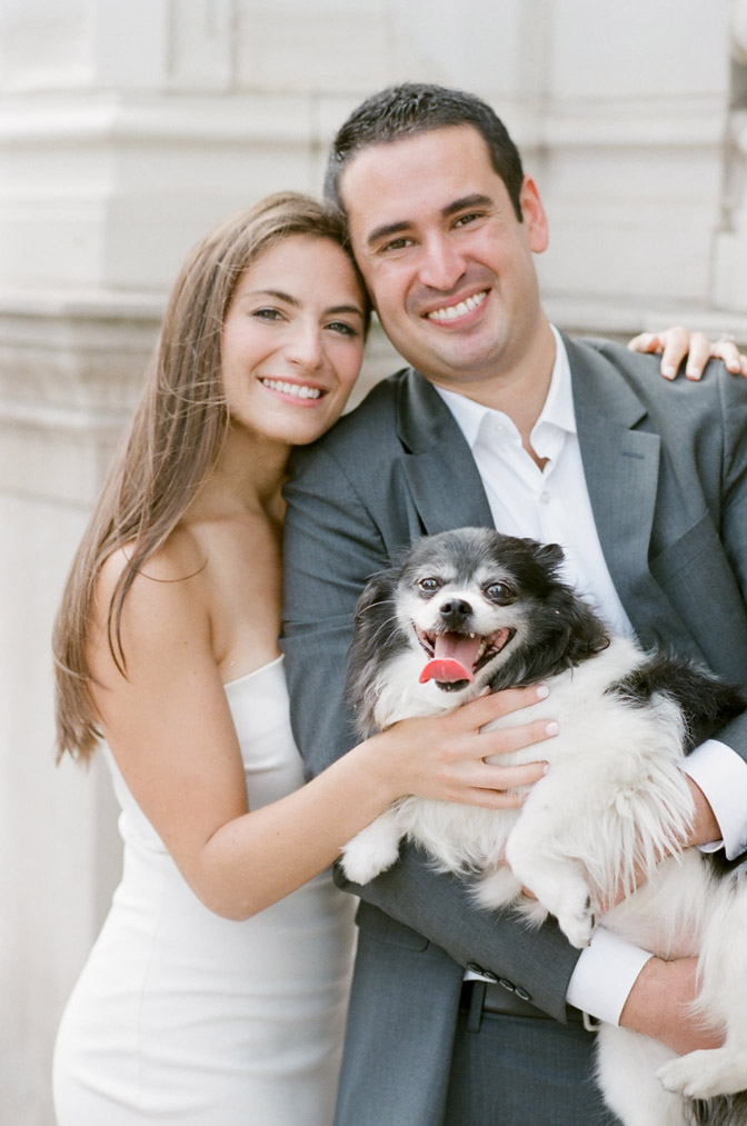 Couple poses for engagement portraits near the Wrigley Building in Chicago with their dog