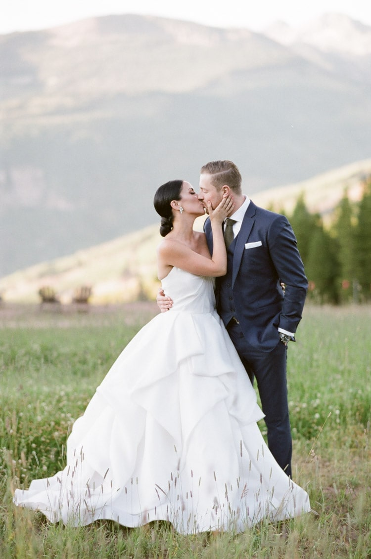Wedding couple kissing in Vail, Colorado with backdrop of mountains