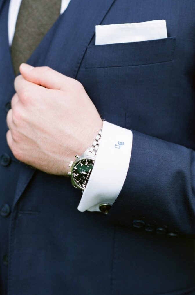 Closeup of man's silver watch and white shirt's sleeve with embroidered initials