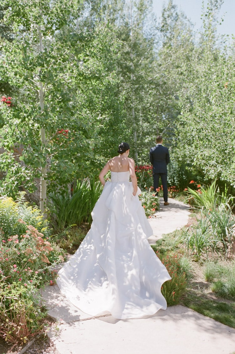 Bride walking towards groom with back turned surrounded by lots of vegetation