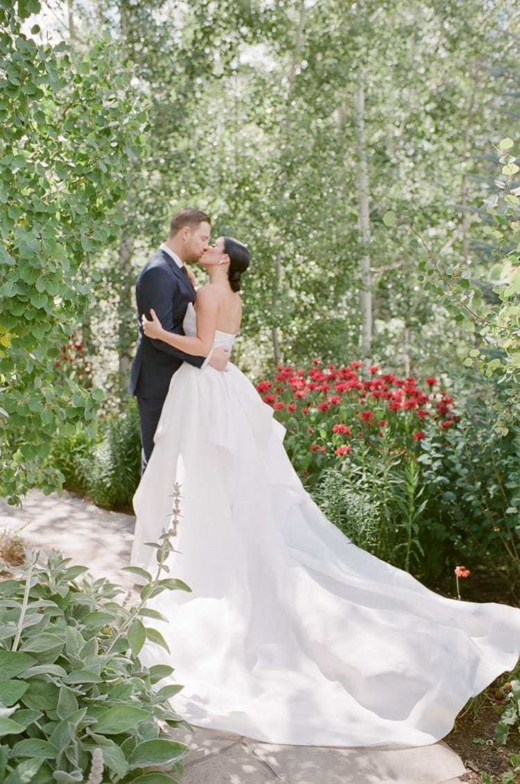 Wedding couple kissing surrounded by greenery and red flowers