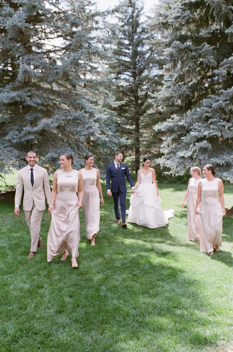 Bridal party walking together with pine trees backdrop