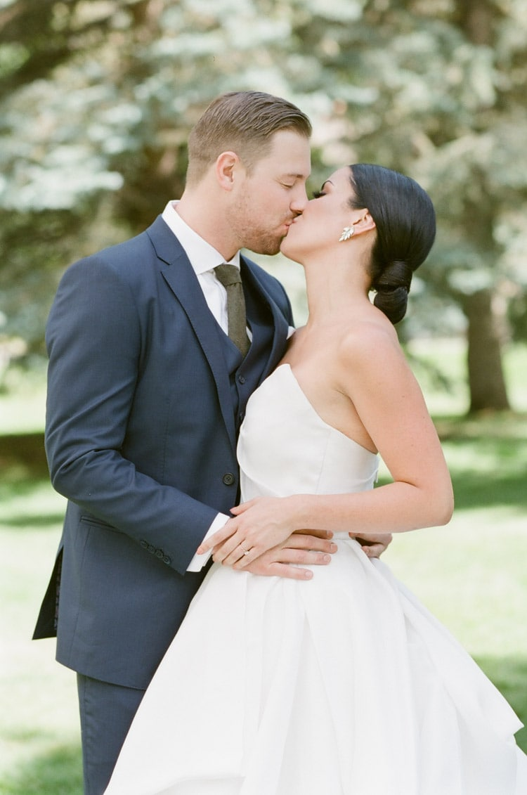 Portrait of bride & groom kissing