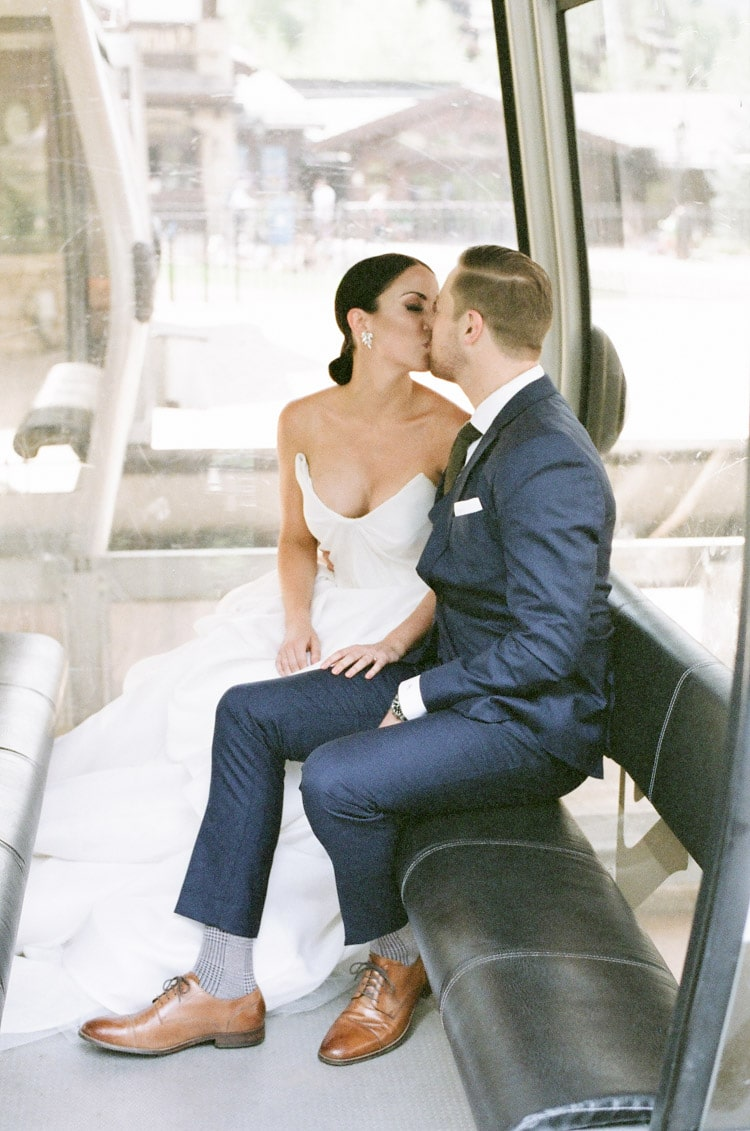 Engaged couple kissing while sitting down on gondola