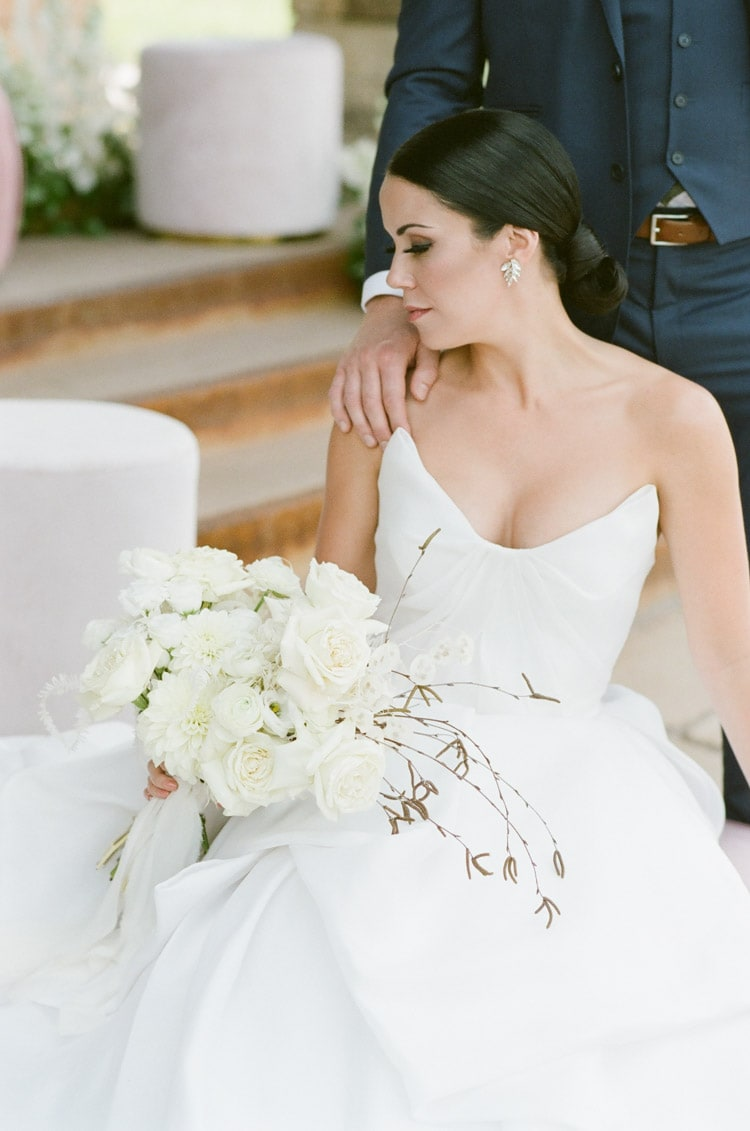 Bride sitting holding white bouquet in white wedding dress