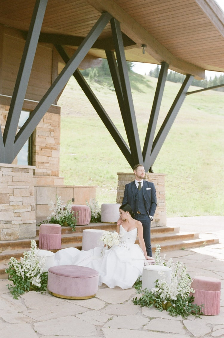 Wedding couple posing under roof of 10th restaurant surrounded by lush, low white and green florals