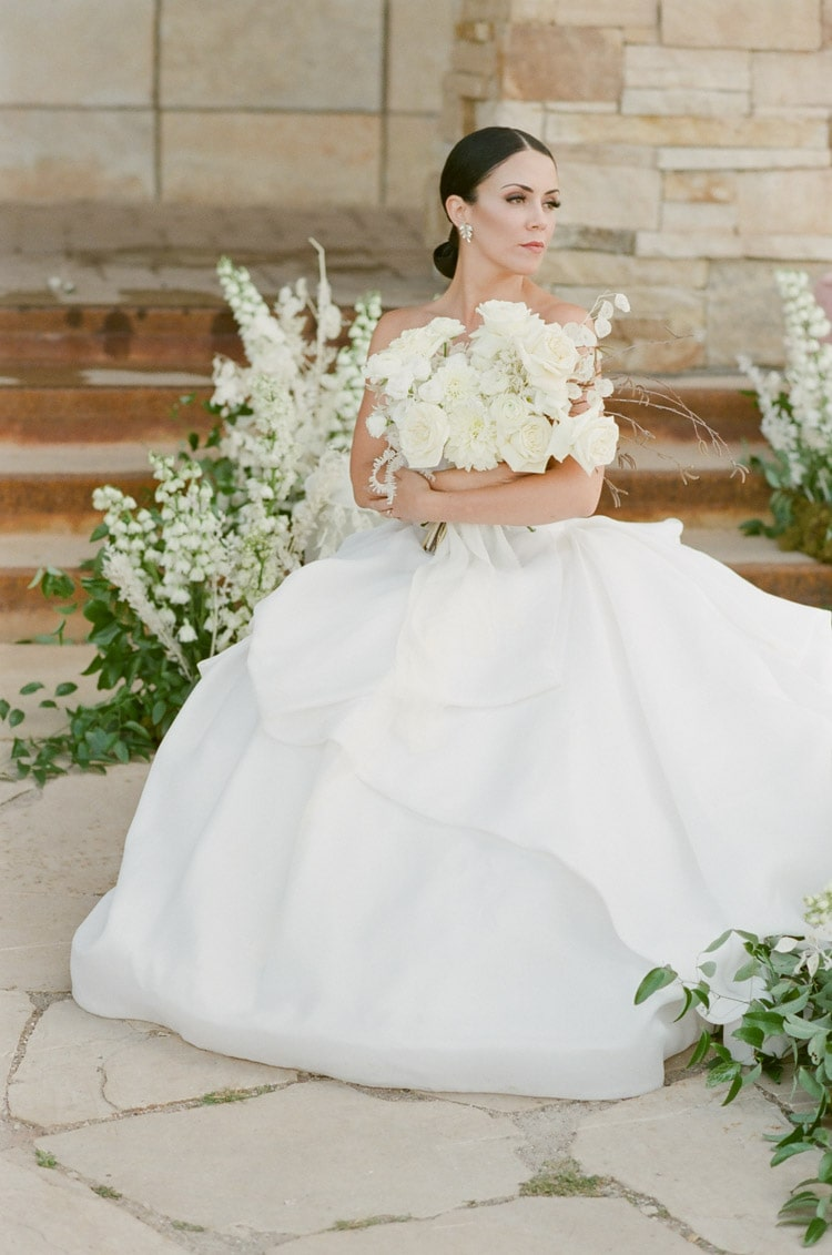 Bride sitting down bidding holding bouquet in arms with large white skirt