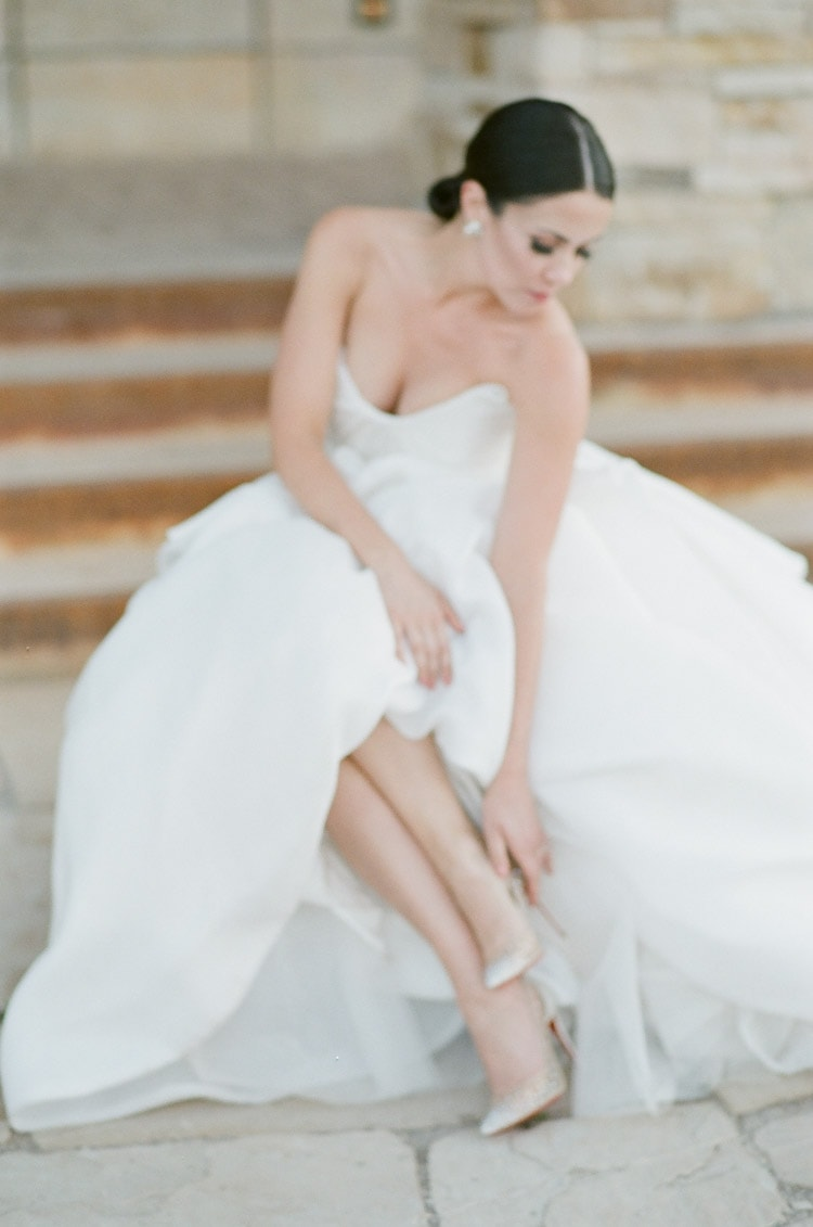 Bride in wedding gown checking heels