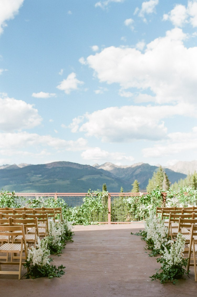 Wedding site ceremony deck with greenery and white floral pieces with stunning views of both the Gore Range and the Vail Valley