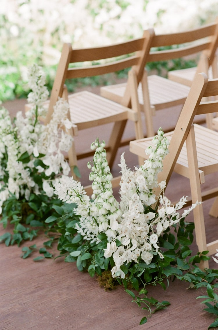 Lush, low white and green floral arrangements to adorn the aisle of wedding ceremony