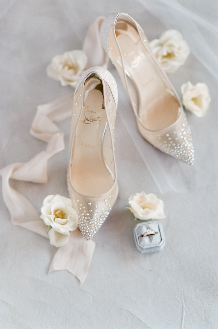 Detailed shot of sparkly Louboutin shoes surrounded by white flowers and wedding ring