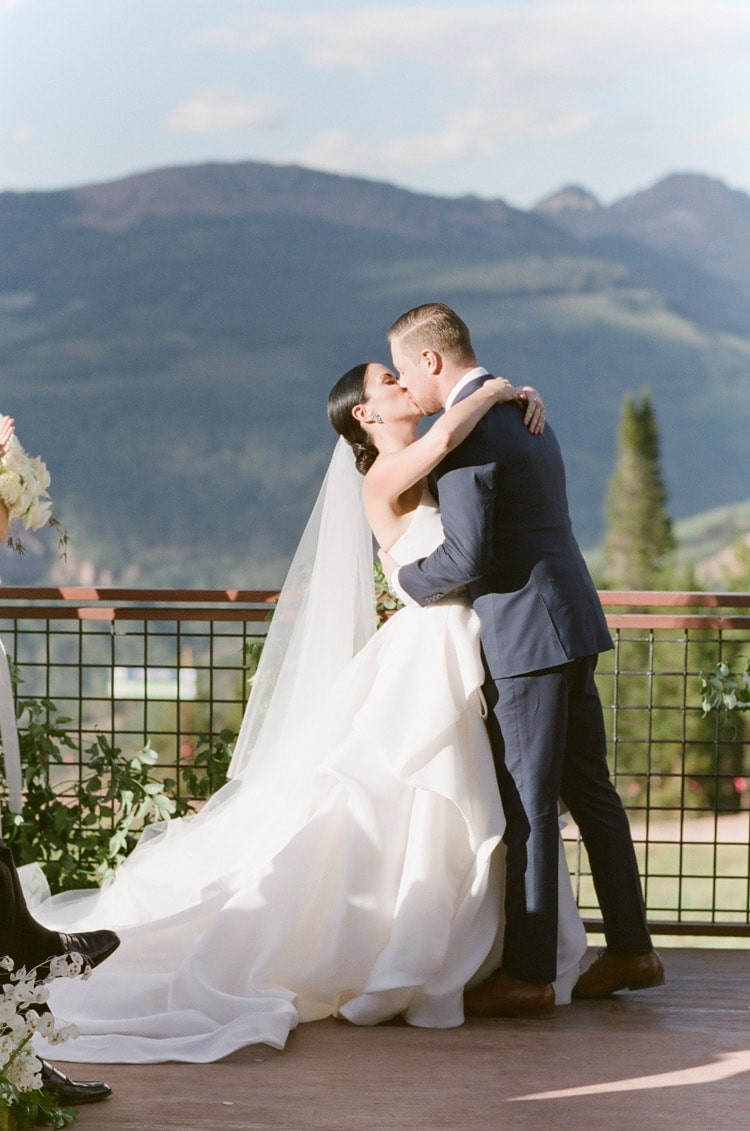 Wedding ceremony first kiss with mountains in backdrop