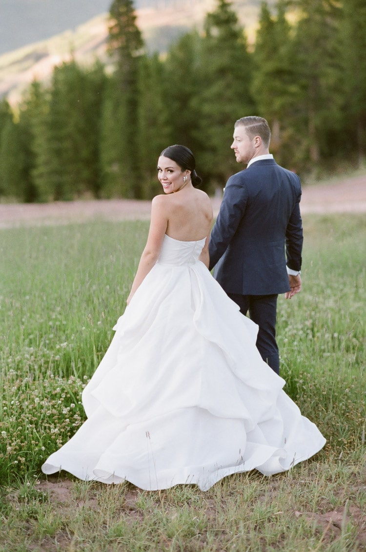Bride and groom walking away in grass with pine trees in the distance
