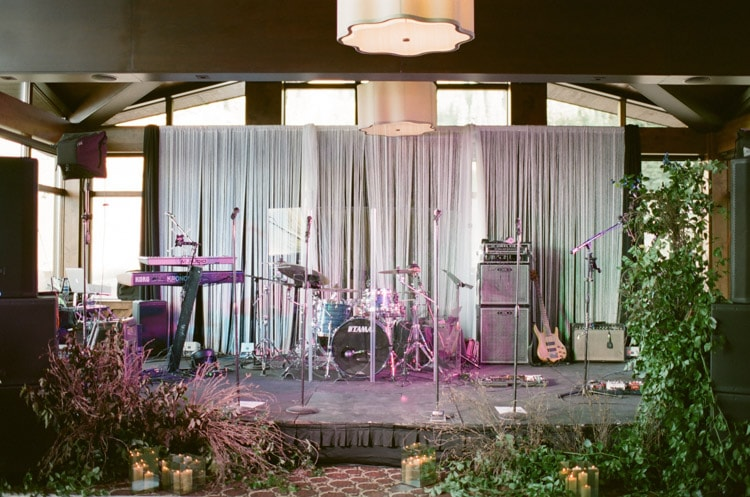 Band stage surrounded by greenery and candles