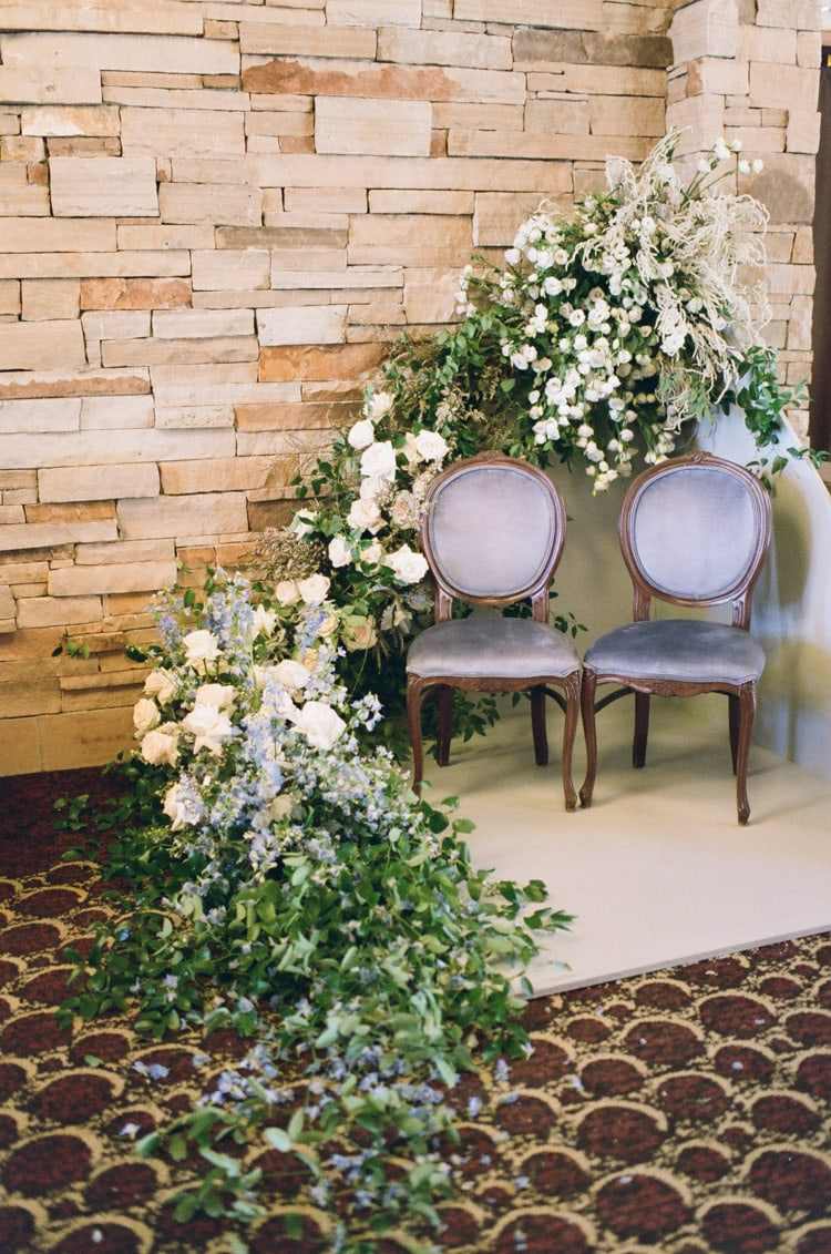 Photo booth featuring two french chairs surrounded by blooms cascading from wall to ground