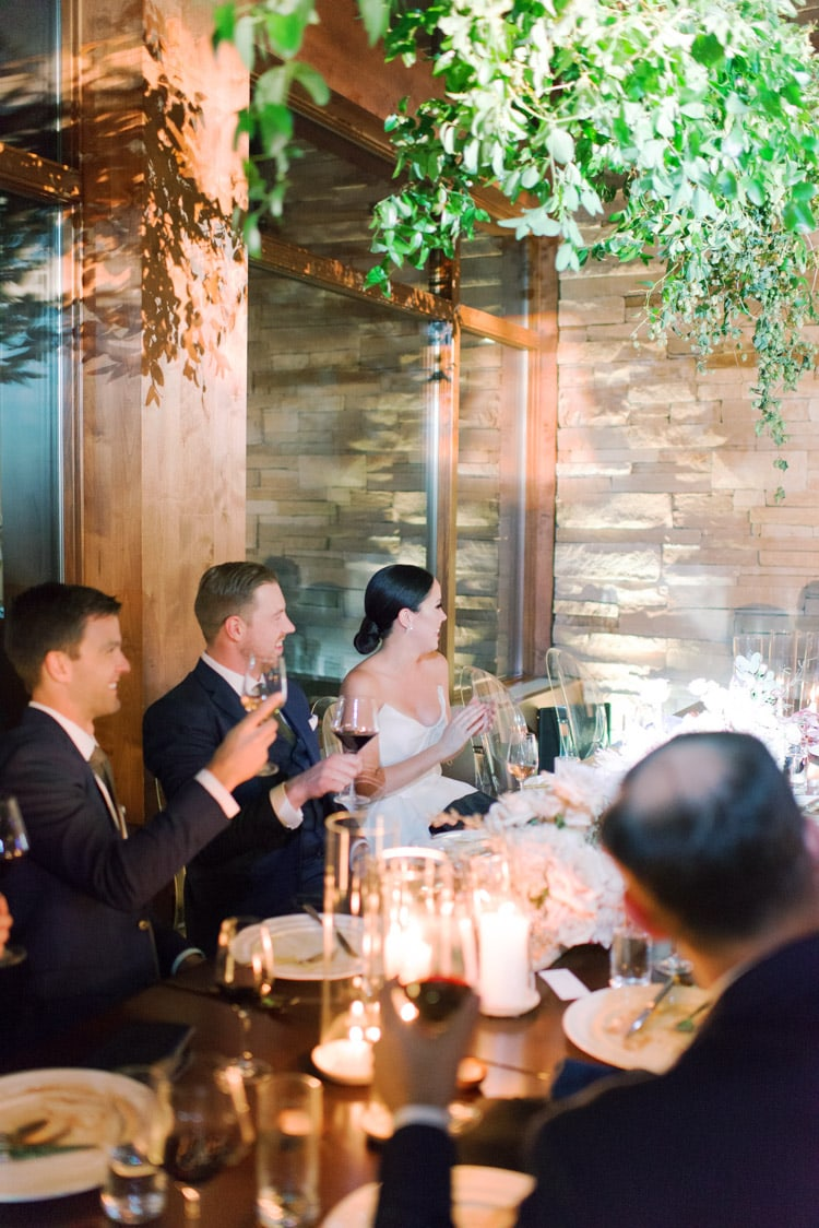 Bride and groom sitting together at wedding reception table with bridal party