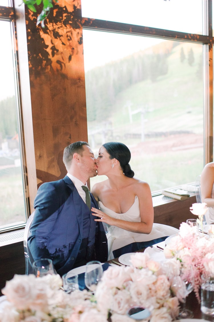 Bride and groom kissing at wedding reception table
