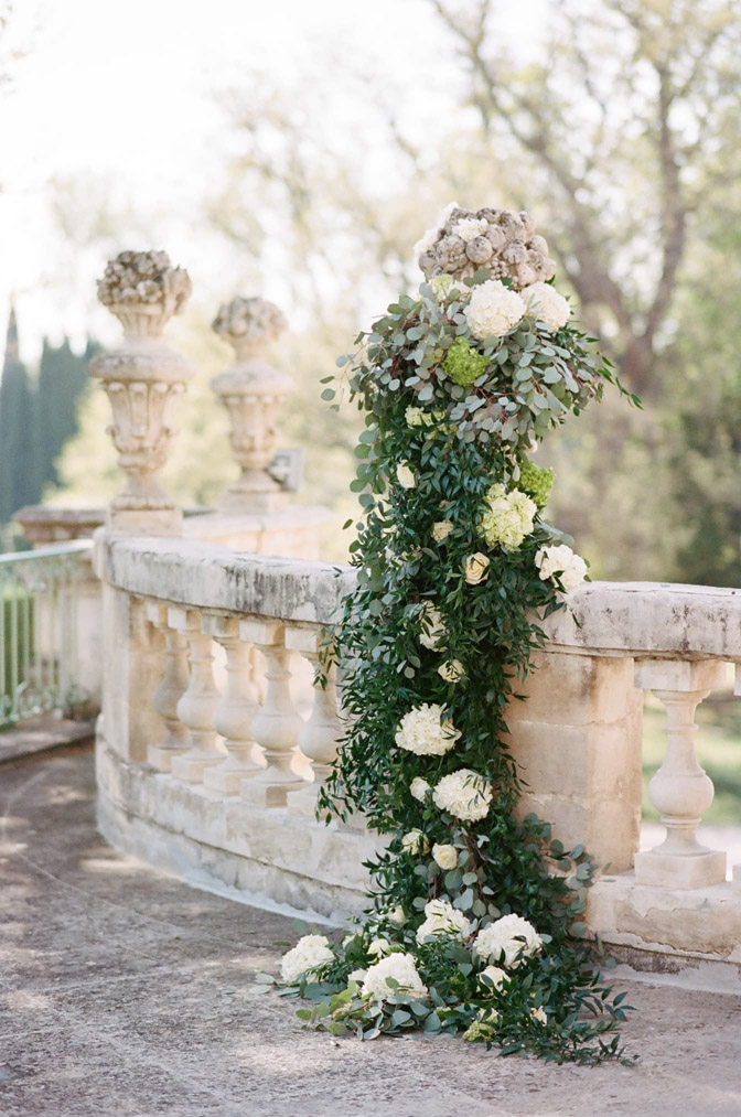 Greenery and white floral decorations on railing
