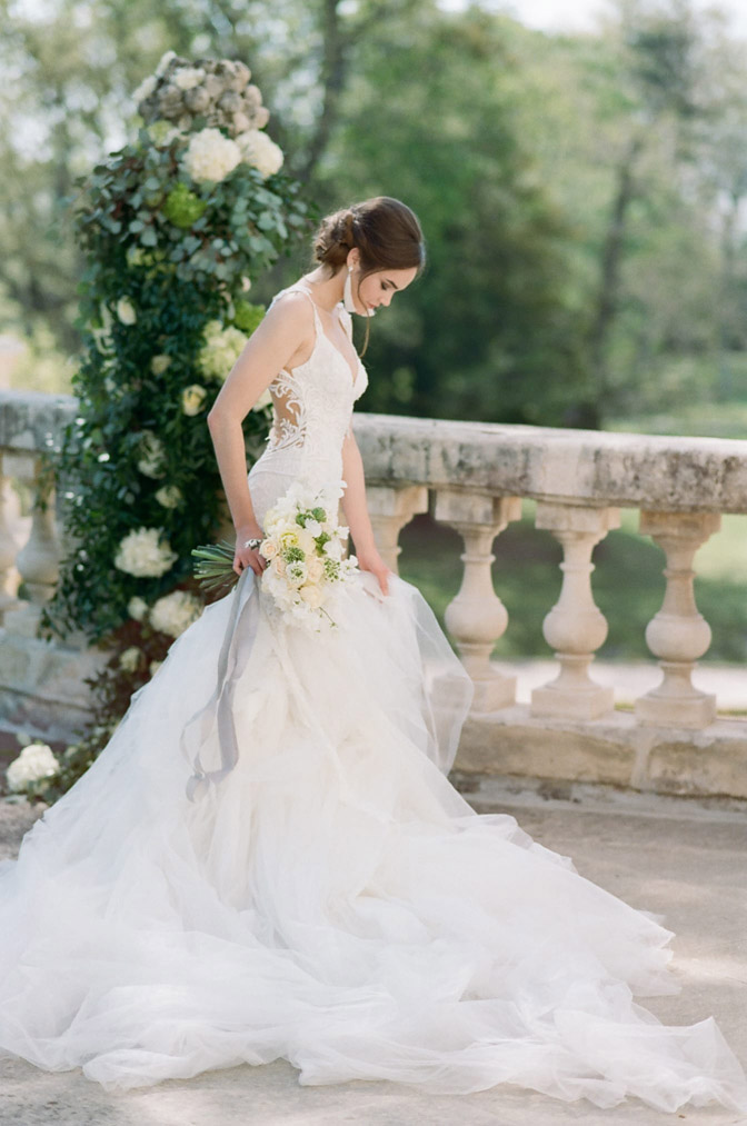 Bride in white lace gown holding bouquet