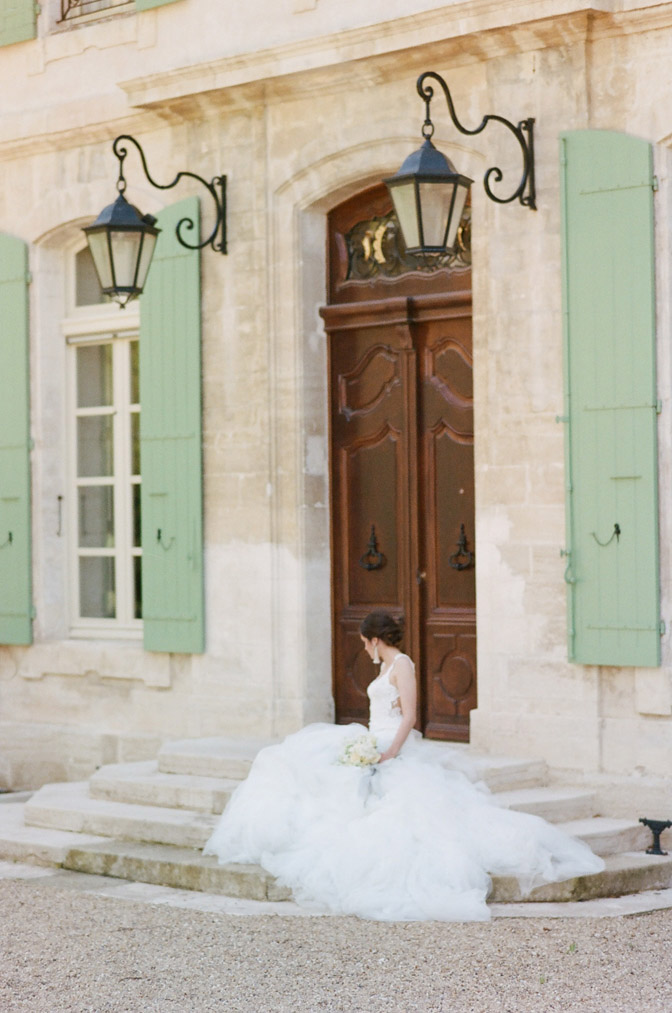Bride sitting on entry steps to Chateau de Tourreau