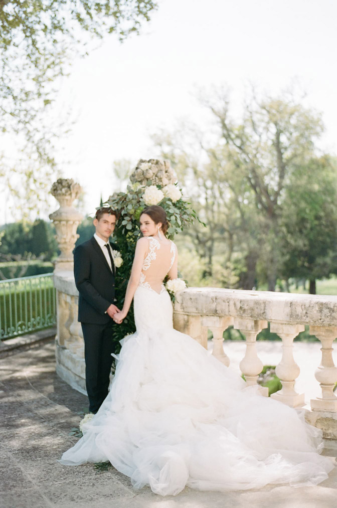 Bride & groom next to detailed stone railing