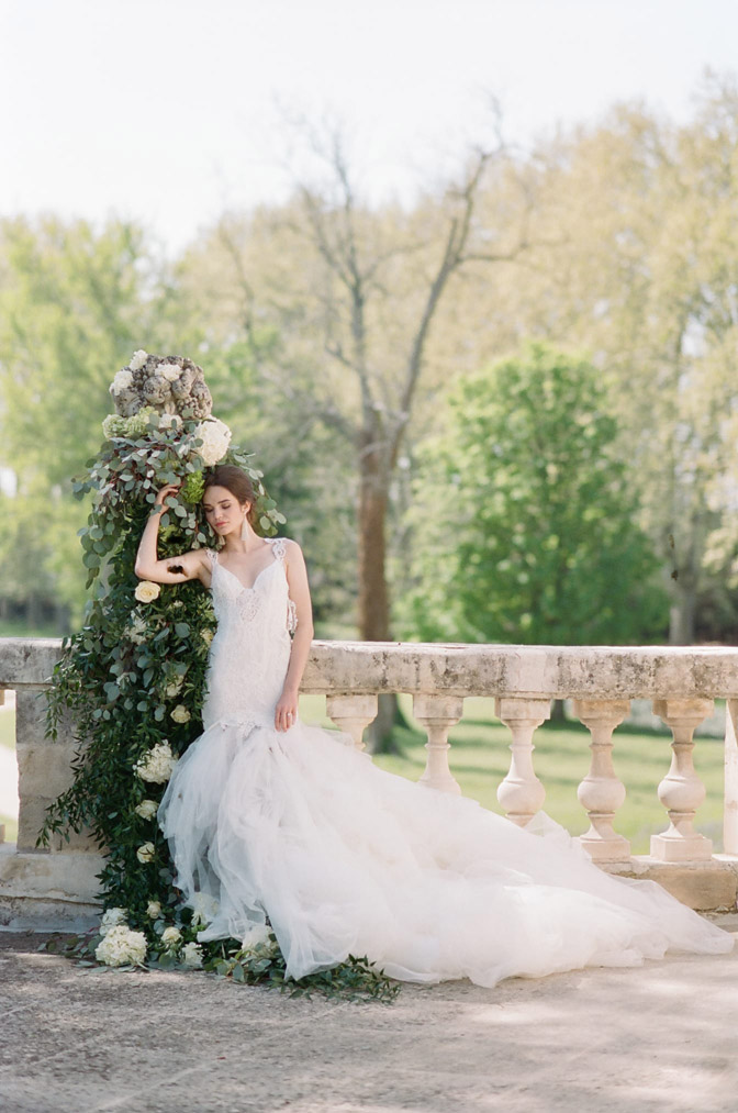Bride leaning against decorated greenery outside