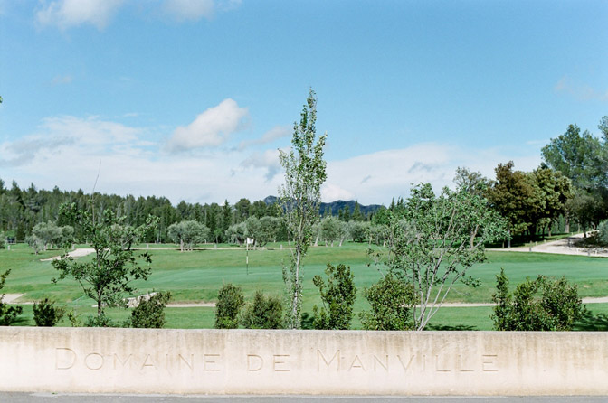 Engraving in stone that says Domaine de Manville with golf course behind it