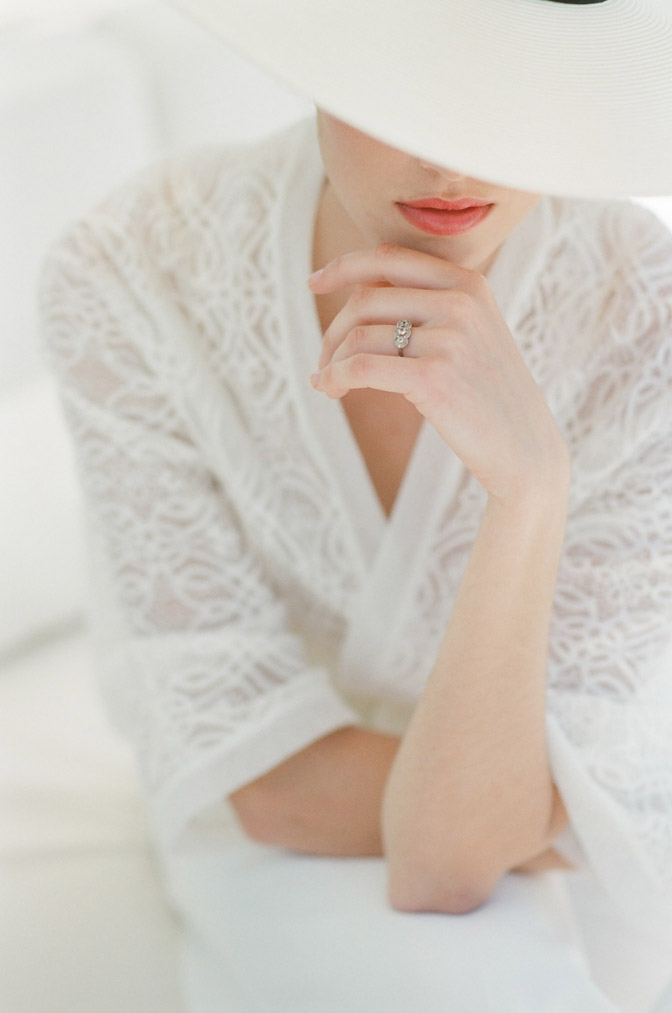 Woman with engagement ring wearing white lace jacket