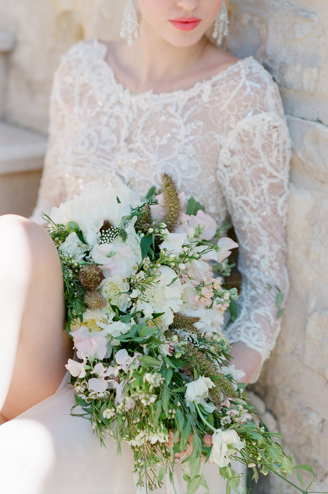 View of bride in white lace wedding dress holding white bouquet