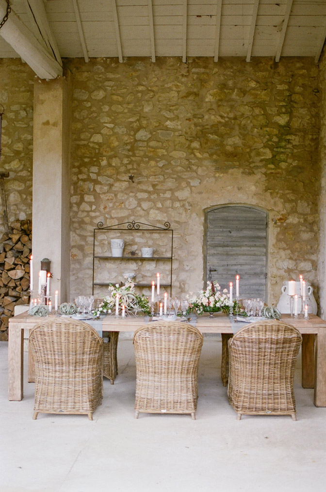 Wedding reception table setup with rustic stone wall background