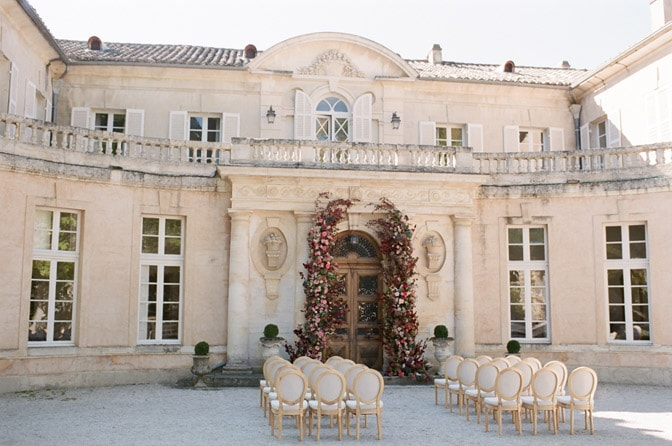 Grand entrance of Château Martinay in Provence accented by florals for a wedding ceremony