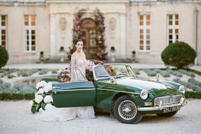 Bride stepping into a classic convertible near her destination wedding ceremony at Château Martinay