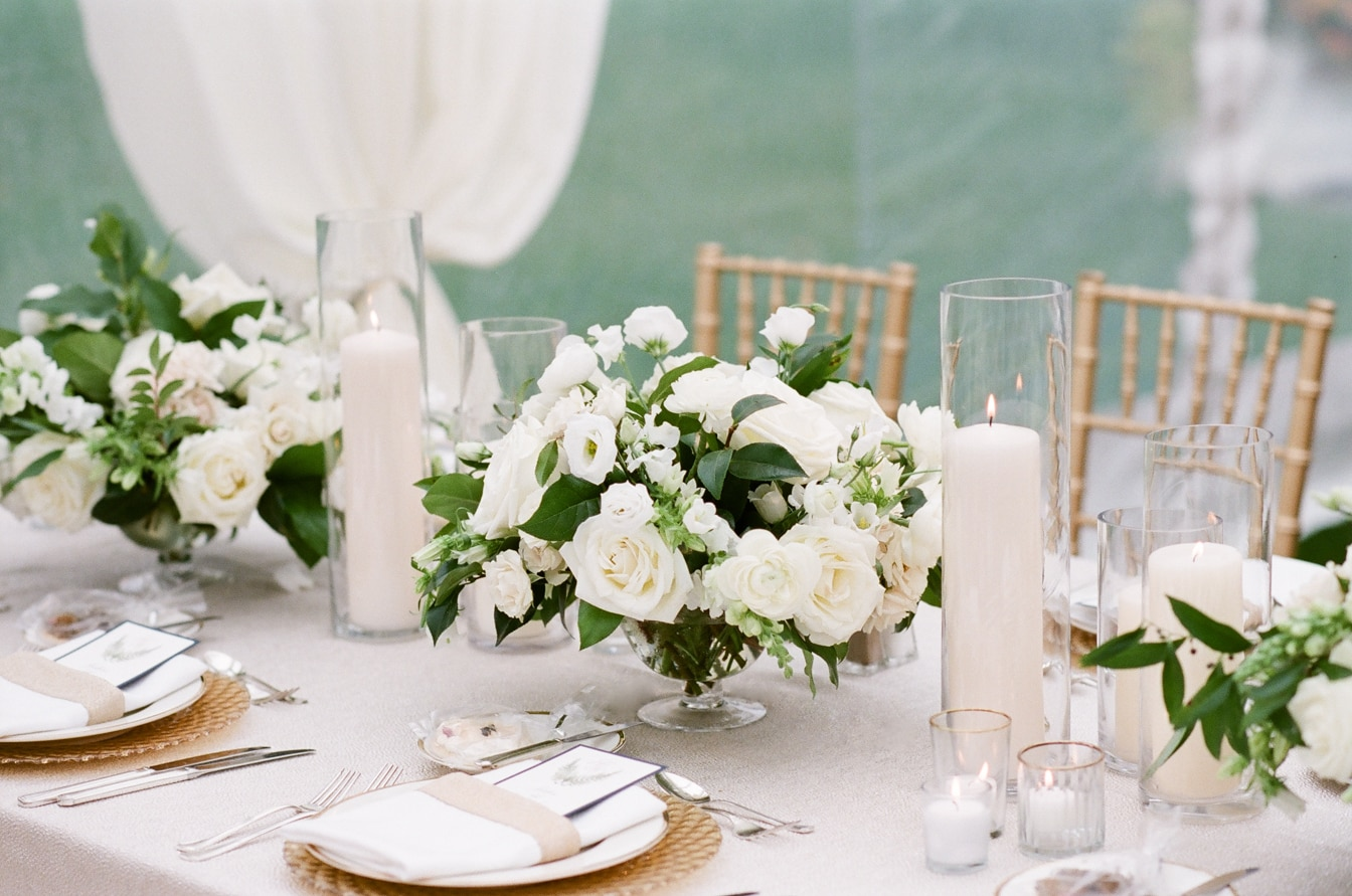 White flowers in vases with surrounding lit candles