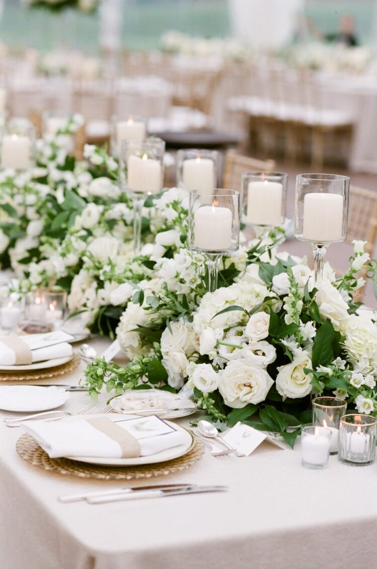 Row of white flower arrangements and candles on table