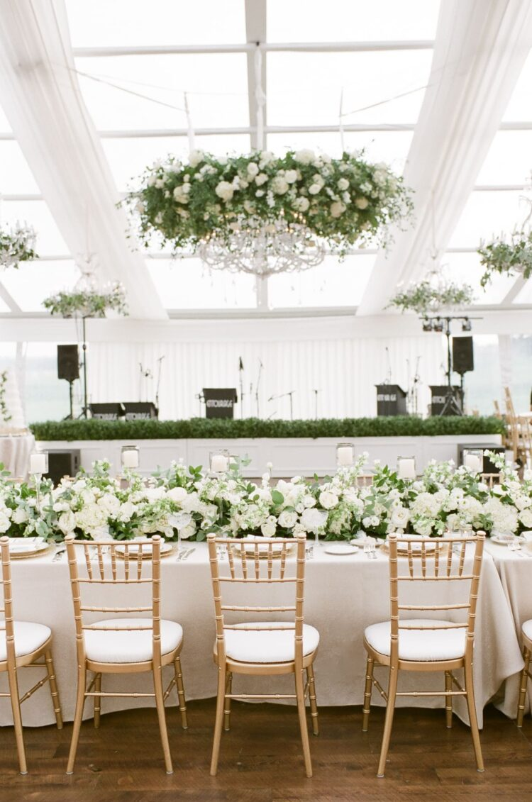 Crystal chandeliers wrapped in greenery hanging in a tented wedding reception in Chicago