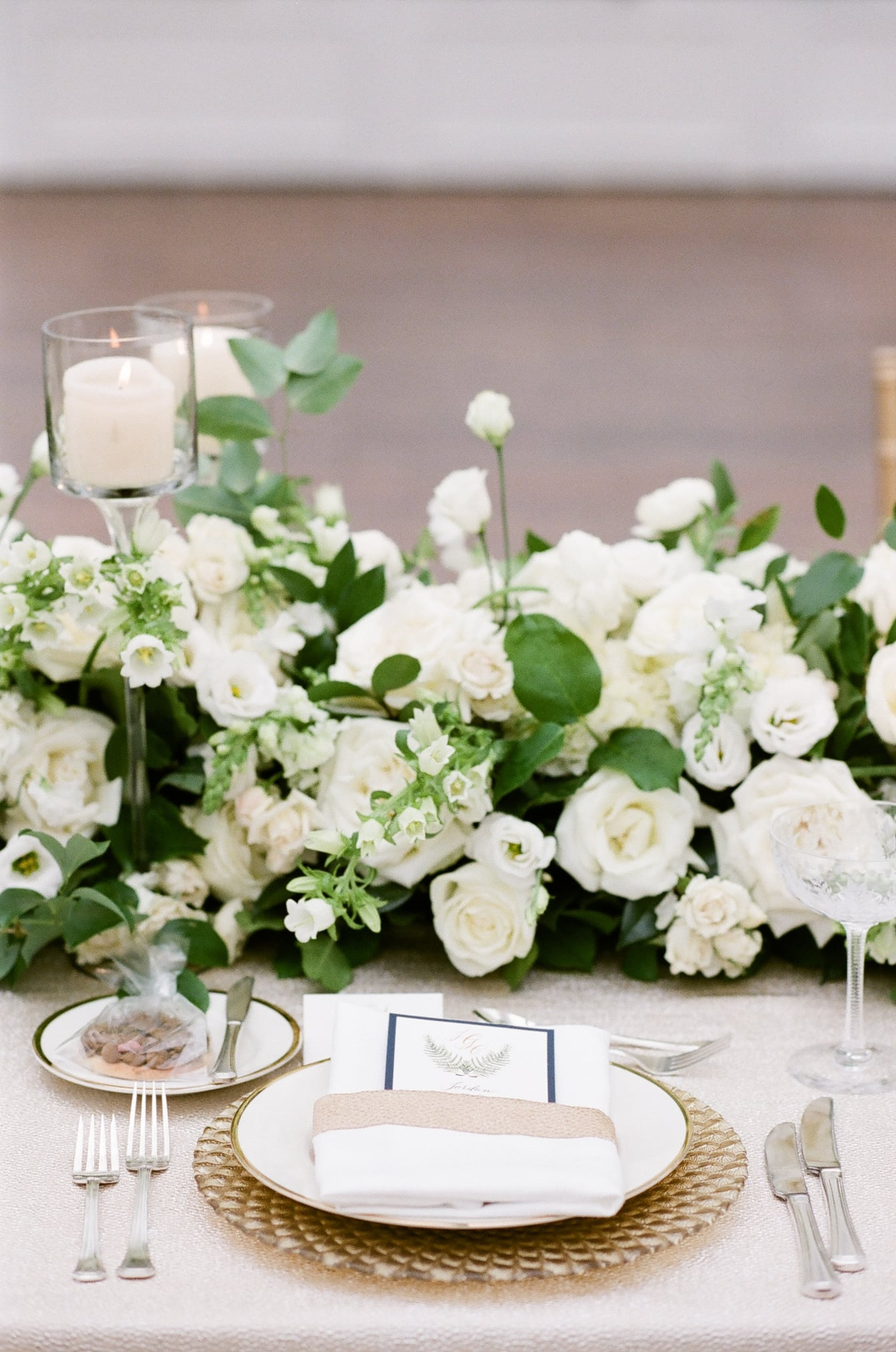 Plate setting with silverware and background of white floral arrangement
