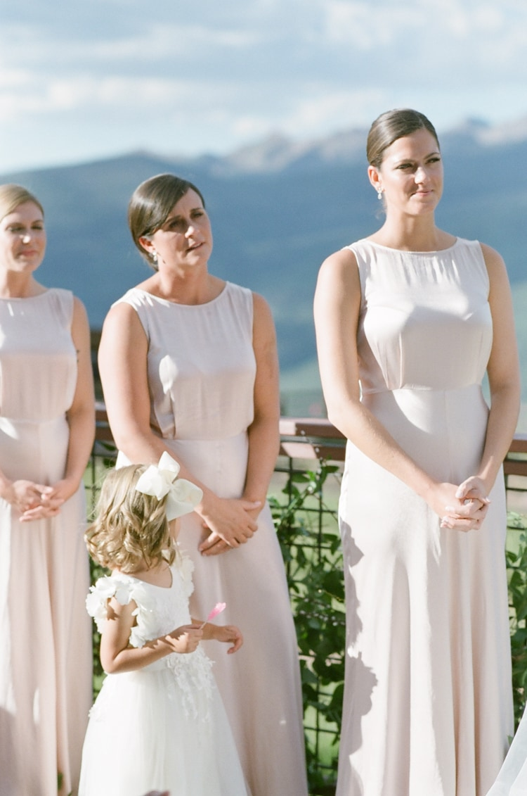 Bridesmaids standing next to ceremony arch and watching wedding ceremony in Vail