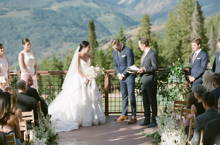 Bride and groom laughing during their wedding ceremony in Vail