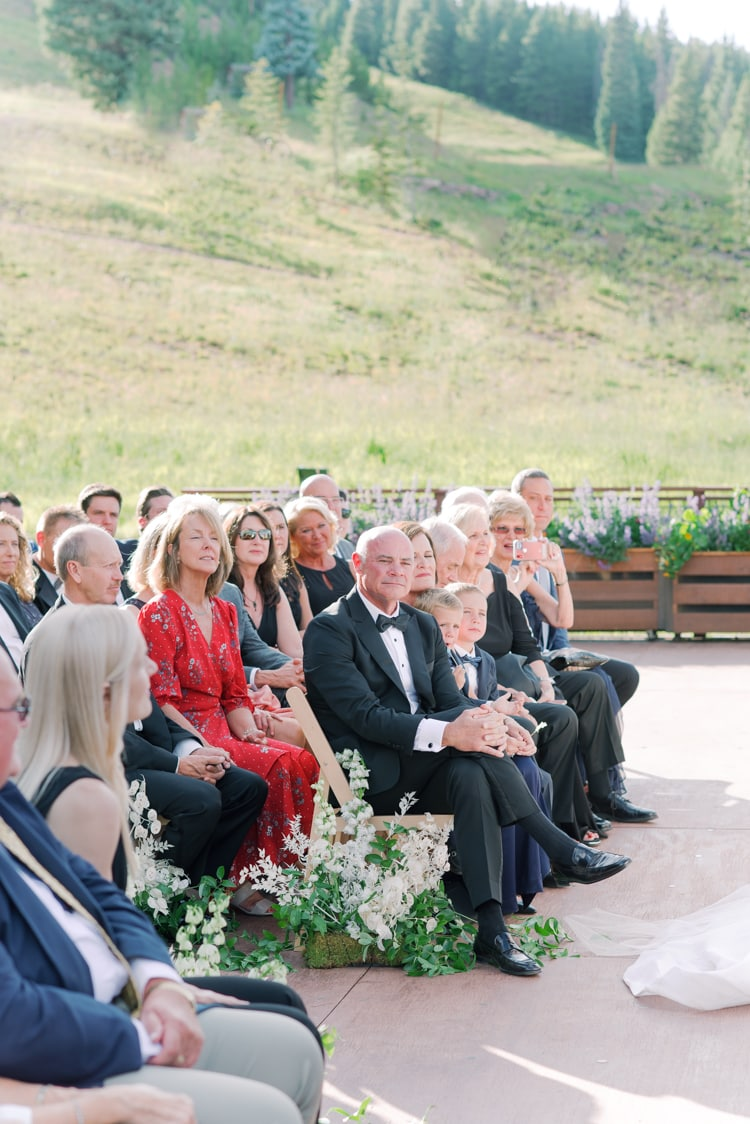Dad and wedding guests watching wedding ceremony at the 10th in Vail