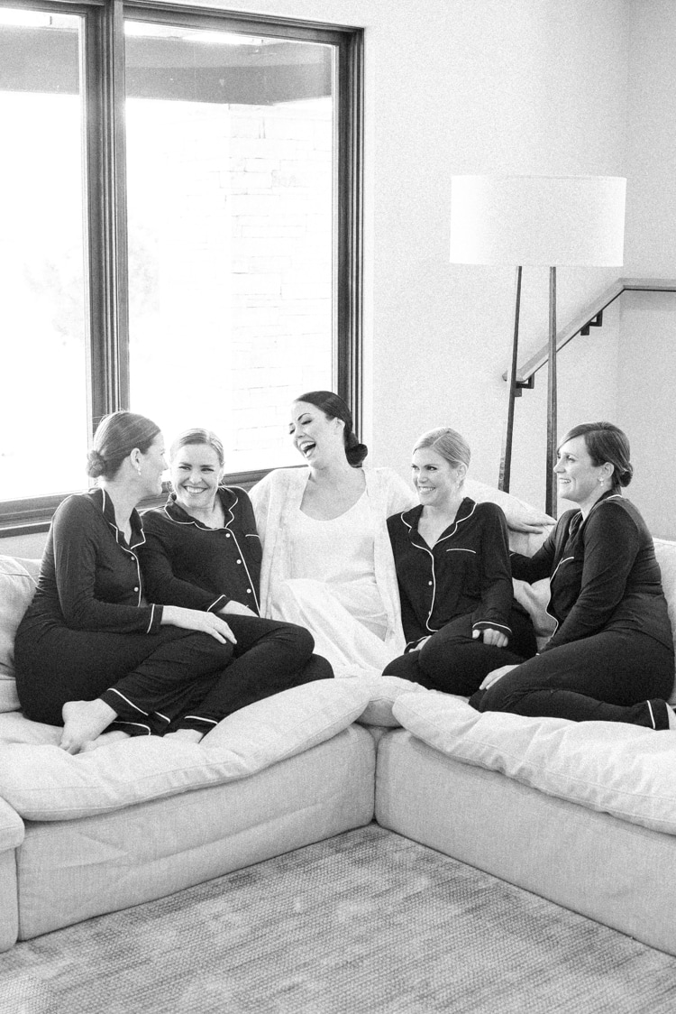 Bride with her bridesmaids sitting on a sofa and laughing together on wedding day