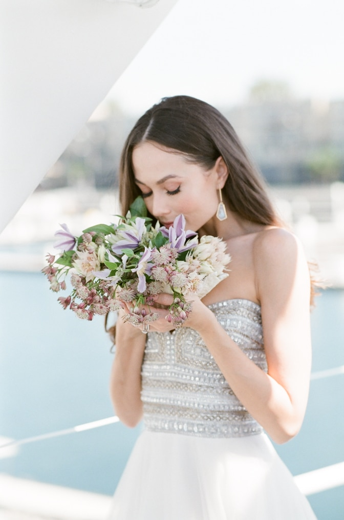 Bride smelling her wedding bouquet on a yacht in Santa Monica, California