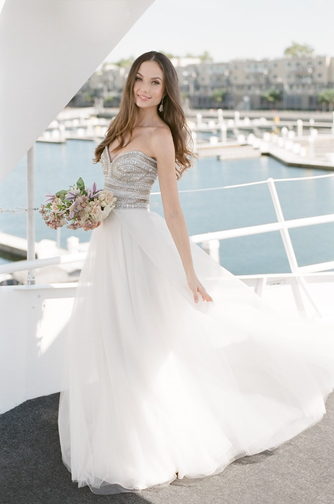 Bride in her Naeem Khan wedding dress on a yacht in a harbor in Santa Monica, California