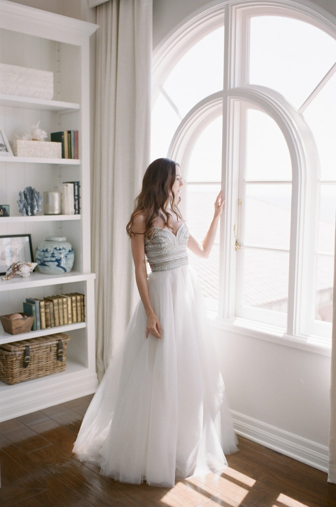 Bride in her Naeem Khan wedding dress looking out the window at Casa del Mar in Santa Monica, California